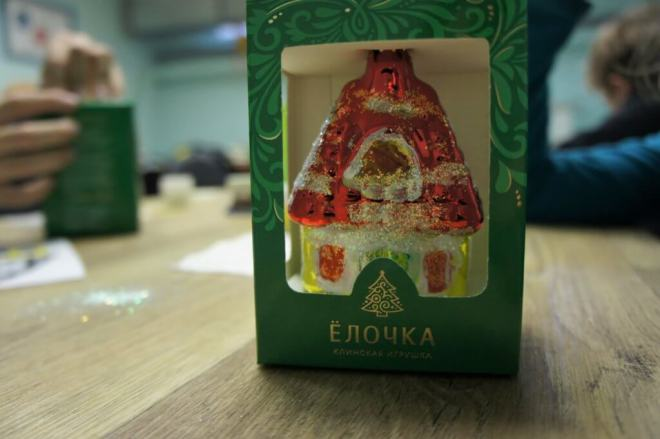 A tree ornament in a green box with the name of the factory, 'Yolochka', on it. The ornament has clearly not been painted by a master.