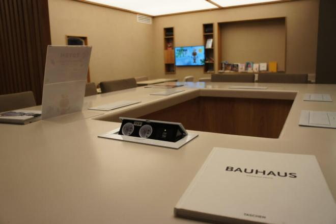 A square workstation with charging sockets in the adult lounge at KidZania Moscow. A TV is on the wall in the background and a Bauhaus artbook on the table in the foreground.
