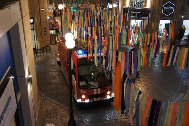 A view of a model fire engine from above as it drives along a KidZania Moscow street. Bunting is hung across the street.