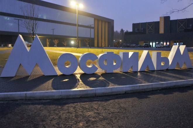 A large white logo saying MOSFILM in Russian stands in front of some modern buildings on the MosFilm Studio tour.