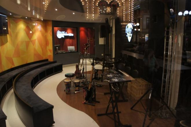 A music studio with various instruments such as drums and a guitar on the right and padded benches on the left