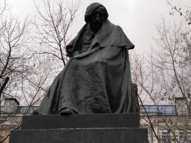 A famously gloomy sculpture of Nikolai Gogol, who sits enshrouded by a cape