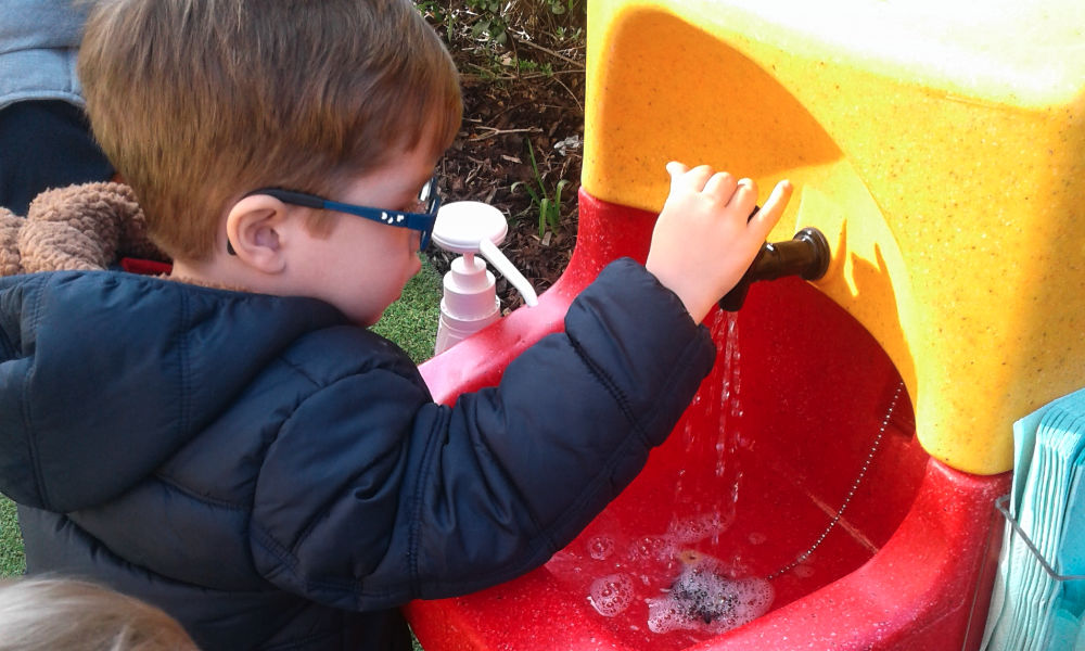 Child washing his hands outside with a KiddiSynk portable sink
