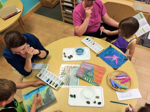 Families make landscapes on sand paper with chalk and watercolors during a session on Impressionism