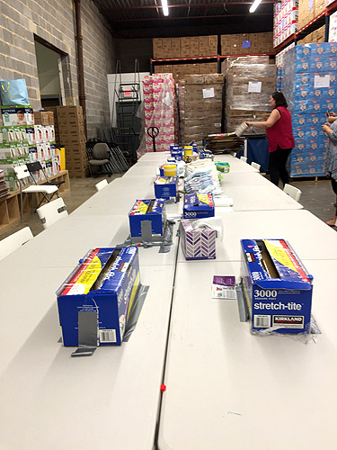 Volunteers tables where diapers are bundled to prep for distribution