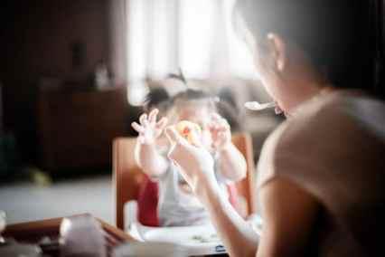une maman qui sonne à manger à sa petite fille