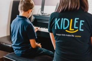 Site de babysitting :  une babysitter Kidlee en train d'apprendre le piano à un petit garçon