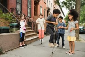 kids playing on pogo sticks outside