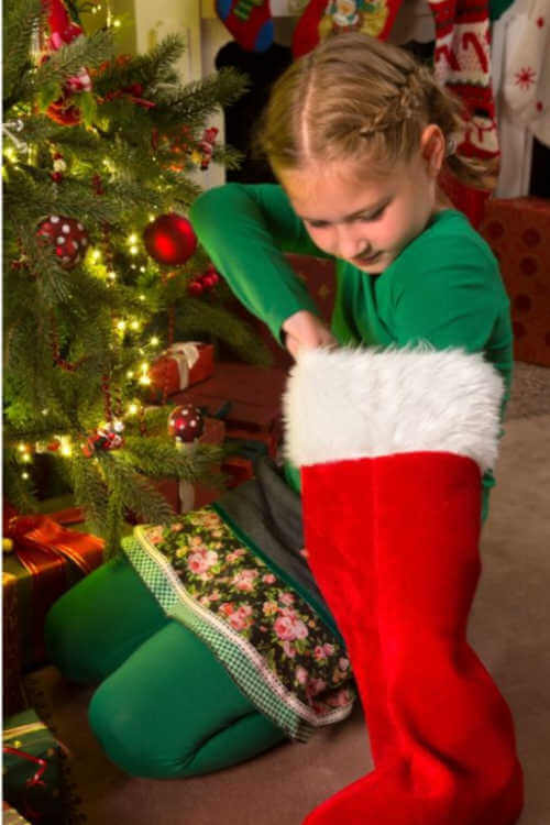 girl reaching in holiday stocking Christmas-Kids Are A Trip