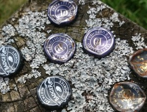 Image of metal beer bottle caps tops lids embedded in wooden fence post
