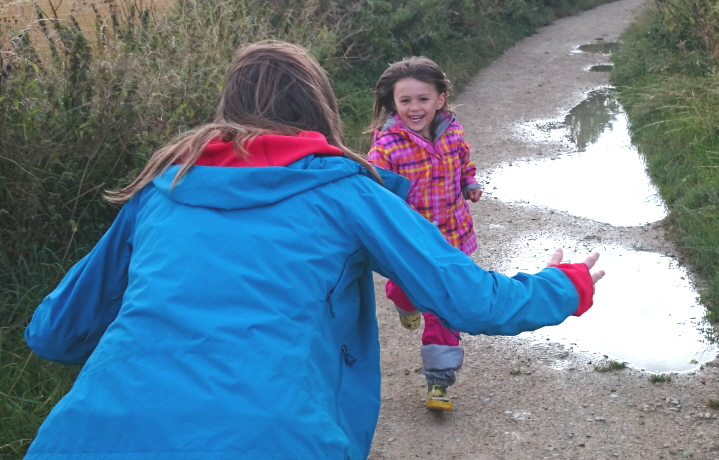 Image of child grinning girl in multi-coloured jacket running towards woman in blue coat with outstrectched arms and hair blowing behind