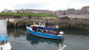 blue-and-white-boat-leaving-seahouse-harbour