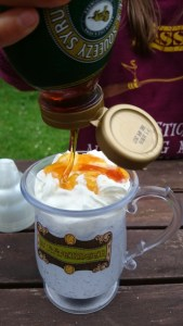 Image of butterscotch-sauce-being-poured-on-cream-topped-tankard