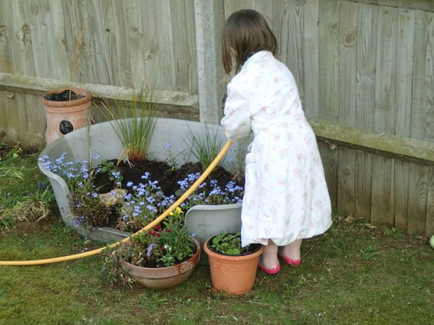 Image of child watering container garden with hose