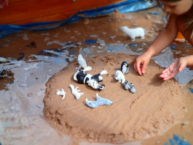 Child playing in sandpit with water and animals