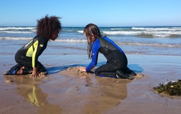 Image of two girls-in-wetsuits-kneeling-on-sandy beach making sand piles with breakers behind