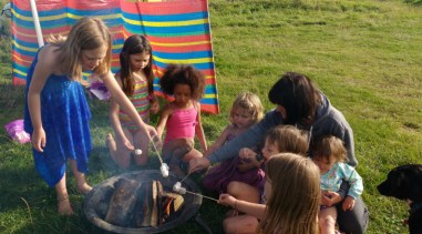 Image of group-of-children-cooking-marshmallows-around-firepit