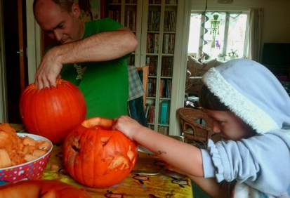 Image of man-and-girl-carving-pumpkins-at-a-table-with-skeleton-in-background