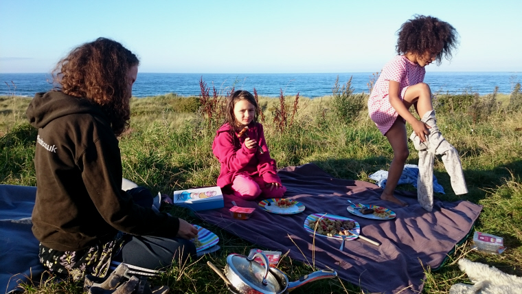 Image of two-girls-and-woman-having-meal-on-rug-overlooking-the-sea
