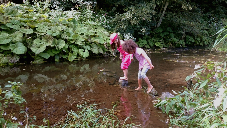 Image of two-girls-crossing-stream-on-steping-stones
