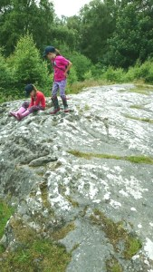 Image of children in pink and red tops with dark caps sitting on rock art, cup holes