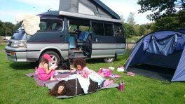 Image of woman-and-two-girls-on-rug-outside-tent-and-camper-van