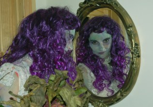 Image of woman-looking-in-mirror-with-purple-wig-halloween-fancy-dress