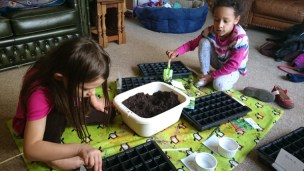 Image of two girls filling seed trays with compost