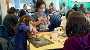 Image of children-at-tables-making-clay-pots