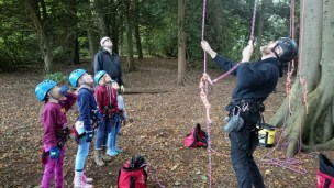 Image of children-being-given-demonstration-with-climbing-ropes-at-bottom-of-tree