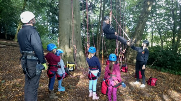 Image of children-with-climbing-ropes-being-given-demo-at-bottom-of-tree