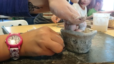Image of close-up-of-childs-hands-decorating-clay-pot-with-pine-cone-patterns