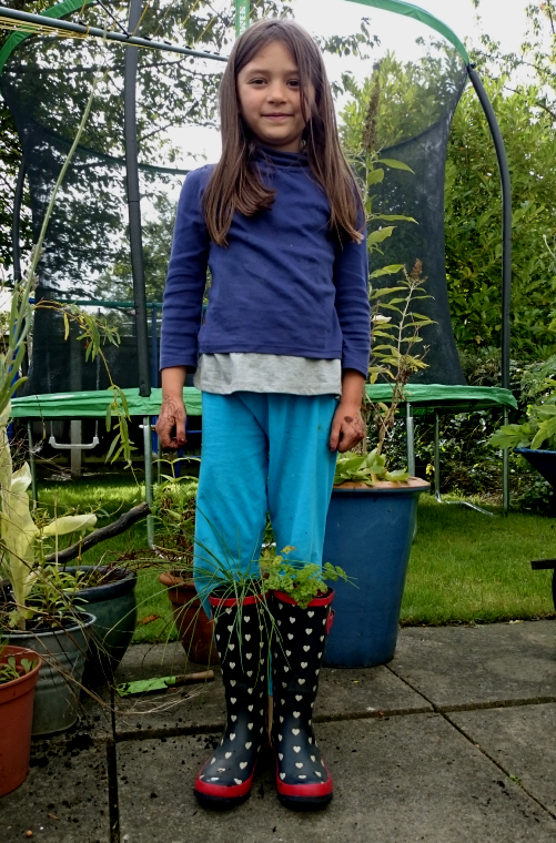 Image of girl-standing-behind-pair-of-wellies-with-herbs-growing-in-as-though-wearing-them