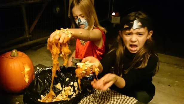 Image of two girls in hallowe'en costume making disgusted faces with hands dripping in pumpkin guts