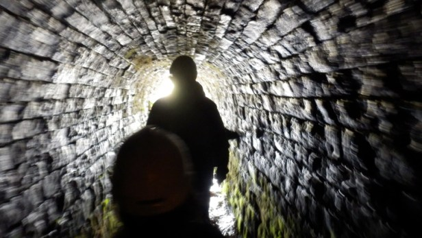 silhouette figures in mining-tunnel