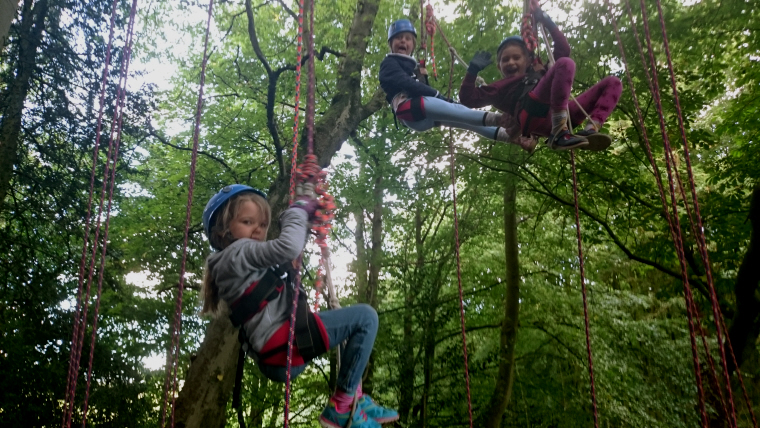 Image of three-girls-in-climbing-harnesses-in-tree