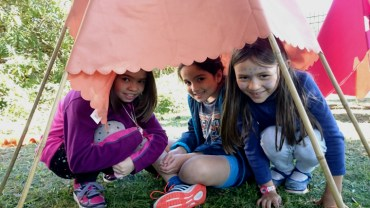 Image of three children peeping from underneath a tipi