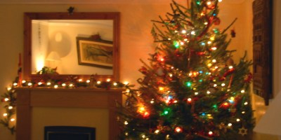 Image of christmas-tree-and-fireplace-decorated-with-lights