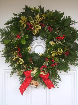 Image of evergreen-christmas-wreath-with-berries-and-red-ribbon-hanging-on-white-door
