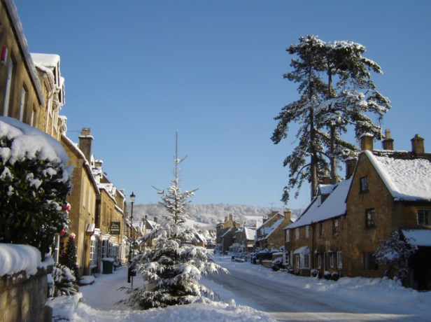 Image of snow-covered-village-street-with-christmas-tree-and-blue-sky