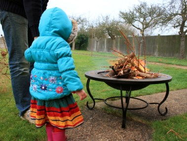 Image of toddler-standing-watching-burning-christmas-tree-branches-in-firepit