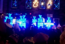 Image of band-of-drummers-in-light-suits-and-white-makeup-on-platform-with-crowd-watching