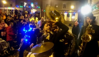 Image of brass-quartet-playing-in-street-with-crowd-and-christmas-lights