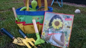 Image of children's pocketed bag with mini gardening tools and book on grass