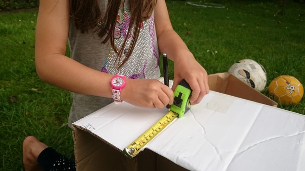 Girl marking measurements on cardboard box