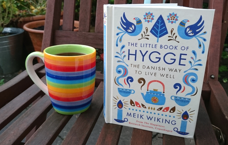 Image of open-book-standing-on-outdoor-chair-with-rainbow-coloured-mug