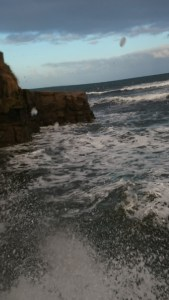 Image of railings-with-sea-behind-and-wave-splashing-on-camera-lens
