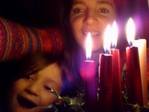 Image of woman and child's faces behind lit candles