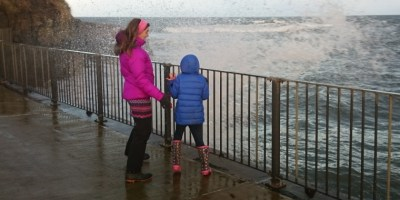 Image of woman-in-purple-coat-and-child-in-blue-coat-being-splashed-by-waves-near-railings-at-the-sea