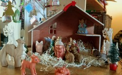 Image of wooden-advent-crib-with-nativity-animals-and-figurines-inside-on-straw-bedding